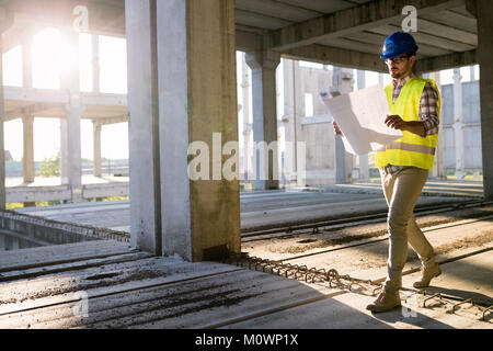 Picture of construction site engineer looking at plan - Stock Photo