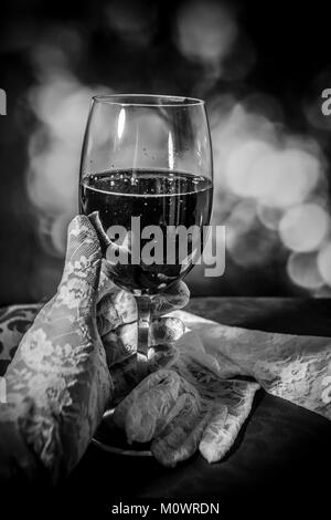 A black and white photo of a hand in white glove holding a glass of wine - Stock Photo