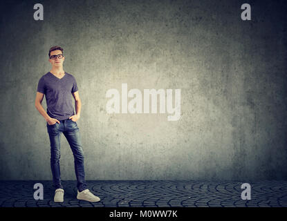 Young modern man in casual outfit posing with hands in pockets looking at camera on gray. - Stock Photo