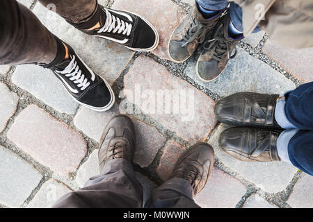 Feet of man, woman, teenager and child. Real family stands together in circle on cobbled street. Top view - Stock Photo