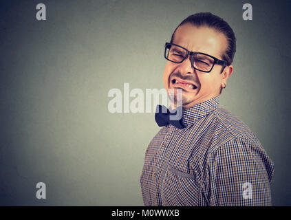 Man in eyeglasses and formal clothing grimacing with disgust on gray background. - Stock Photo