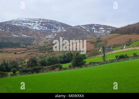 A view across one of the many snow topped hills and valleys of the Mourne Mountains on a dull midwinter afternoon - Stock Photo
