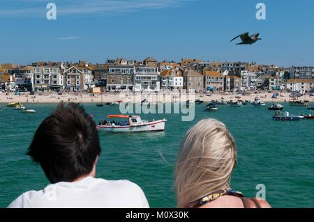 United Kingdom,Cornwall,Saint Ives,couple looking towards the boats and beach - Stock Photo