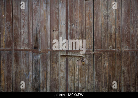 Wooden brown door. Weathered blank, banner, background with rusty latch and padlock. Closeup, detail - Stock Photo