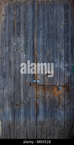 Wooden dark blue, blank, aged, peeled door for backdrop. Rusty latch on doorway. Close up, banner. - Stock Photo