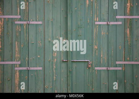 Wooden green door. Weathered blank, banner, background with rusty latch and padlock. Closeup, detail - Stock Photo