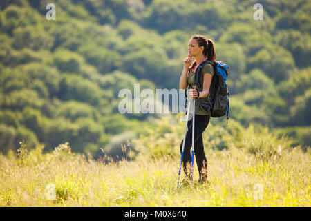 Young woman is hiking in mountain. She is thinking about a way to go. - Stock Photo