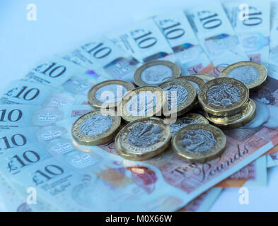 Several new British pound coins lying randomly on a fanned out bed of new polymer ten pound sterling notes - Stock Photo