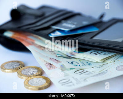 A black wallet containing credit or debit cards and five and ten pound notes fanned out with three pound coins at - Stock Photo