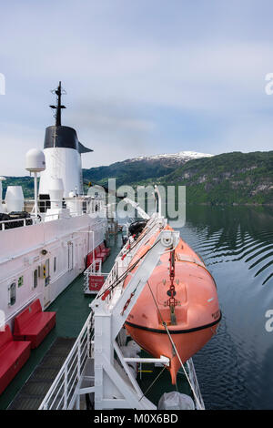 Enclosed lifeboat hanging from davits on side of cruise ship sailing in a fjord. Sogn og Fjordane, Norway, Scandinavia - Stock Photo