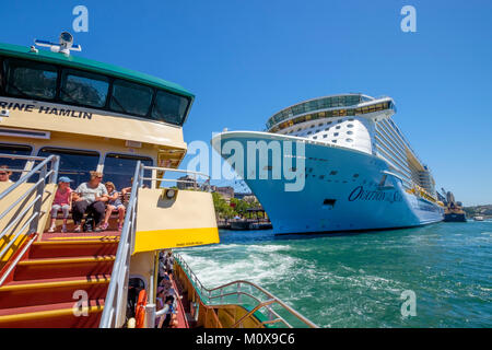 Sydney Ferry ride from Circular Quay. Passing Royal Caribbean's Ovation of the Seas cruise ship moored at Overseas - Stock Photo