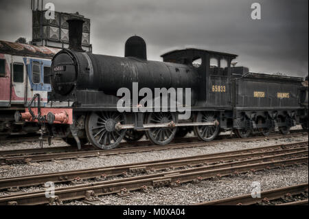 End of the line the British Railways steam train 65033 waits for restoration as it stands outside on the tracks. - Stock Photo