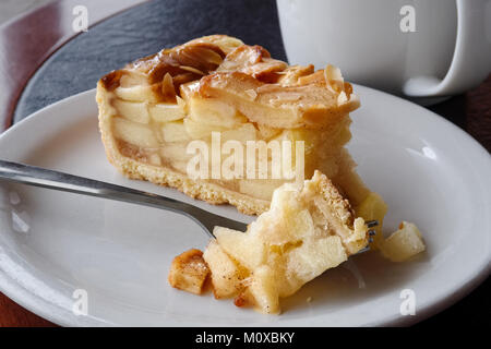 A slice of apple pie with pie on fork on white ceramic plate next to a fork. Black and brown table. - Stock Photo