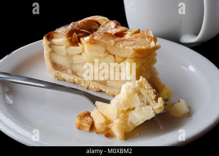 A slice of apple pie with pie on fork on white ceramic plate next to a fork. Black background. - Stock Photo