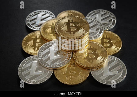 Pyramid from bitcoins and litecoins with stack of coins on the top - Stock Photo