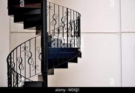 Elegant metal exterior spiral staircase on the side of a house in Singapore - Stock Photo