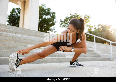 Portrait of a fitness woman doing stretching exercises on stairs outdoors - Stock Photo