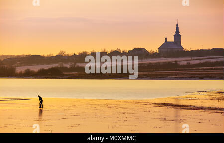 undefined person skating on the frozen lake in evening. beautiful winter countryside scenery. village and church - Stock Photo