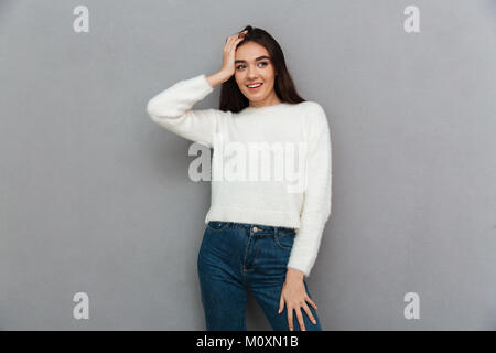 Close-up photo of young smiling woman in casual wear holding her head, looking aside, isolated on gray background - Stock Photo