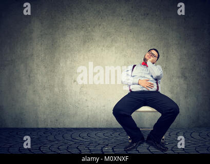 Young chunky man sitting idly on chair and dreaming unwilling to work. - Stock Photo