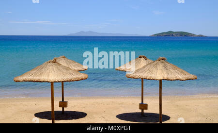 Four straw beach umbrellas on the shore of beautiful blue sea with small islands on the horizon. - Stock Photo