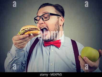 Chubby man in eyeglasses eating burger choosing junk food instead of healthy diet. - Stock Photo