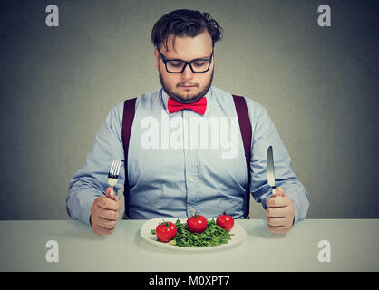 Young overweight man concentrated on healthy salad trying to lose weight. - Stock Photo