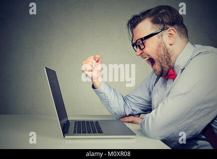 Side view of chubby young man in formal screaming in frustration while working with laptop. - Stock Photo