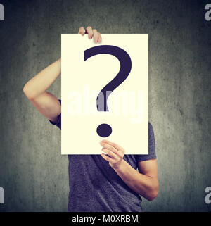 Casual anonymous man covering face with paper showing question mark. - Stock Photo