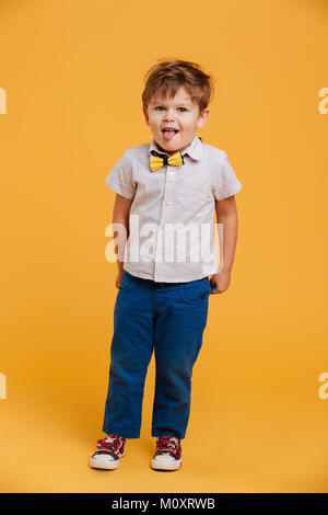 Photo of little boy child standing isolated over yellow background. Looking camera showing tongue. - Stock Photo