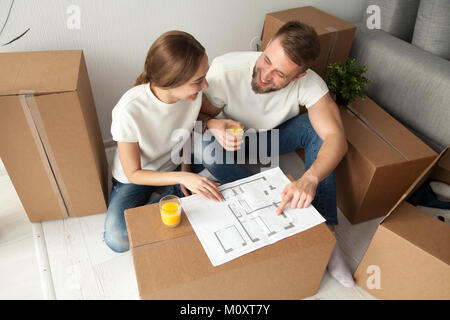 Couple discussing house plan sitting on floor with moving boxes - Stock Photo