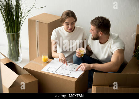 Couple agreeing on home interior design with house plan together - Stock Photo