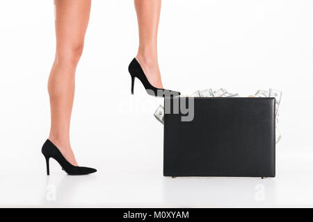 Close up portrait of a female legs wearing high heels standing with a briefcase full of money banknotes isolated - Stock Photo