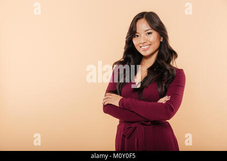 Portrait of elegant asian female in pretty maroon dress posing on camera with arms folded, isolated over peach background - Stock Photo