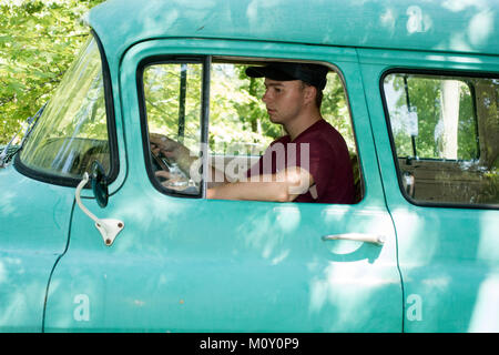 Teenage boy driving a 1956 Chevy Suburban Carryall performing chores on his family summer property. Clitherall Minnesota - Stock Photo