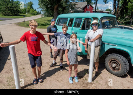 Family standing beside their 1956 Chevy Suburban Carryall, ready to drive back to the cottage after a malt shop - Stock Photo