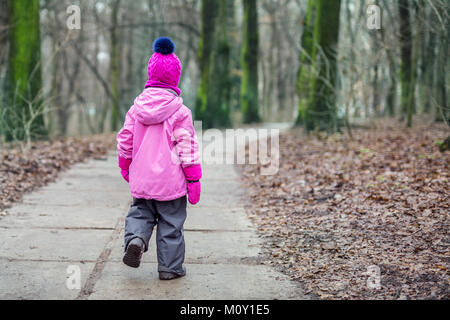 Little  girl walking alone in a forest  at autumn - Stock Photo