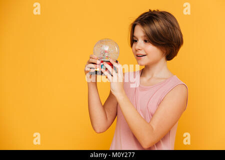 Handsome smiling girl in dress holding and looking at snow globe isolated over yellow - Stock Photo
