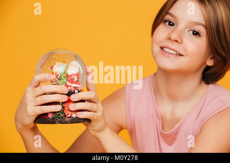 Portrait of beautiful smiling girl in pink dress looking camera and holding snow globe in hands isolated over yellow - Stock Photo