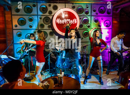 Local live rock band with exotic dancers playing at Woodstock, a night club in downtown Saigon (Ho Chi Minh City), - Stock Photo