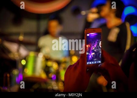 Woman using a mobile phone (cell phone, smartphone, cellphone} taking a picture of a rock band in a night club, Saigon (Ho Chi Minh City), Vietnam