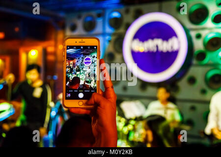 Woman using a mobile phone (cell phone, smartphone, cellphone} taking a picture of a rock band in a night club, - Stock Photo