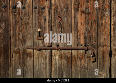 Wooden brown door. Timeworn blank, banner, background with rusty latch and padlock. Closeup, details - Stock Photo