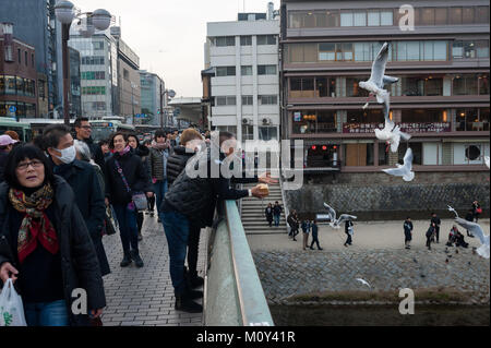 23.12.2017, Kyoto, Japan, Asia - Pedestrians are seen crossing the Shijo Bridge that spans over the Kamo River in - Stock Photo