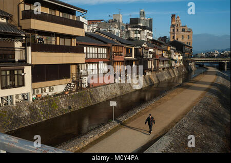 26.12.2017, Kyoto, Japan, Asia - A man is seen strolling down a pathway along the Kamo River in Kyoto at dawn. - Stock Photo