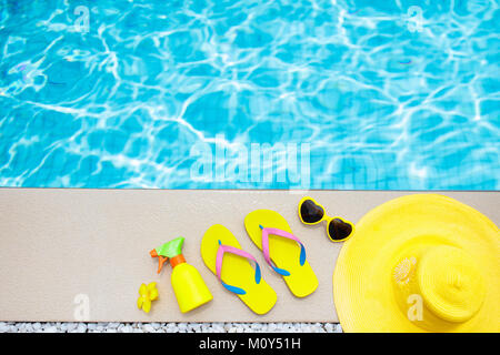 Swimming pool accessories flat lay. Top view of beach items on pool deck. Flip flops, bikini and hat, sun glasses. - Stock Photo
