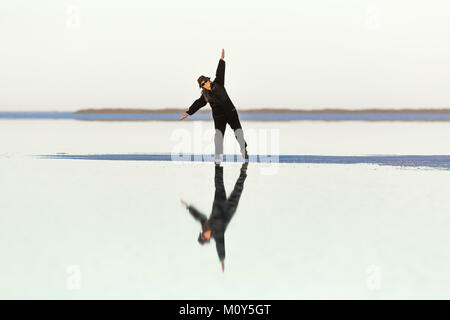 Woman walking on a spit of land extending out into shallow salt water at the Bonneville Salt Flats, in BLM's Special - Stock Photo