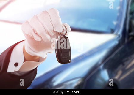 Close-up Of Valet Boy Hand In White Glove Holding Car Key - Stock Photo