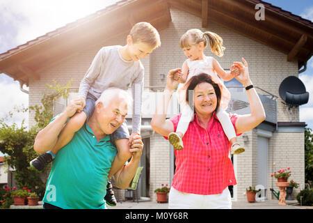 Smiling Grandchildren's Sitting On Grandparent's Shoulder Enjoying Outside Their House - Stock Photo