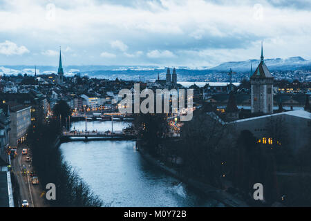 Aerial view of Zurich city center at dawn, with the Limmat river in the foreground and the old town in the background. - Stock Photo